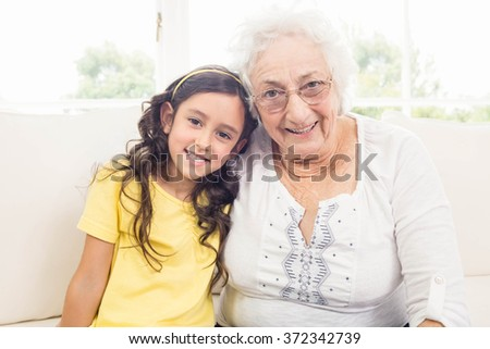 Grandmother and granddaughter smiling at home - stock photo