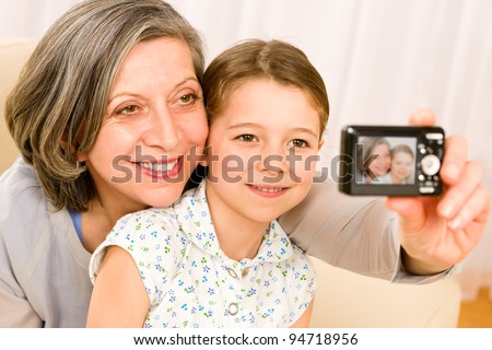 Grandmother and granddaughter take picture themselves smiling close-up portrait - stock photo