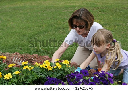 Grandmother and granddaughter tending a garden in a scenic field - stock photo
