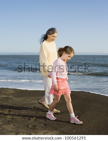 Grandmother and granddaughter walking on the beach