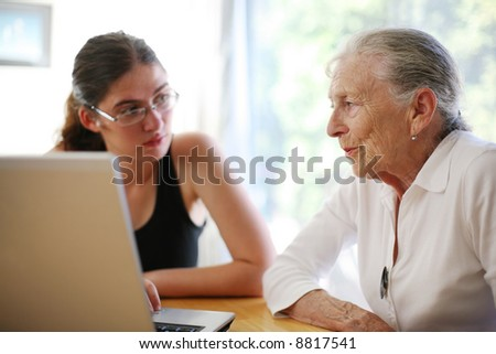 Grandmother and granddaughter with laptop. - stock photo