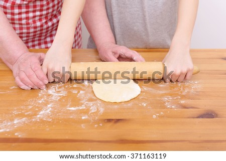 Grandmother and grandson cook dough for baking of sweet