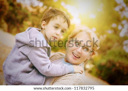 Grandmother and grandson playing in the park - stock photo