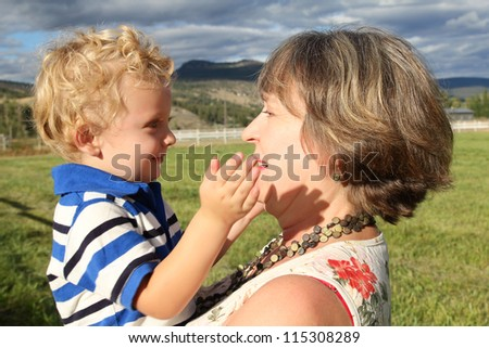 Grandmother and grandson playing outside in the field - stock photo