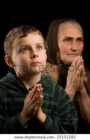 Grandmother and grandson praying together - stock photo