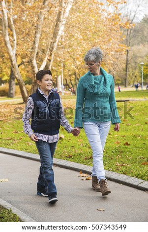 Grandmother and grandson take a walk during the fall of the leaves in the park