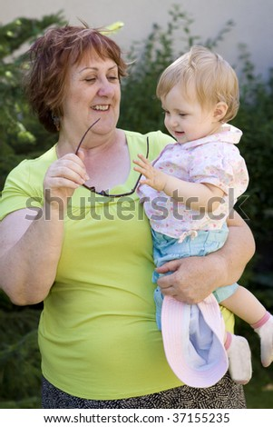 Grandmother and her granddaughter in garden - stock photo
