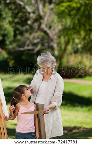 Grandmother and her granddaughter painting in the garden - stock photo
