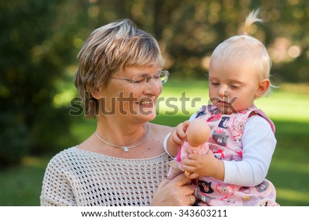 Grandmother and her granddaughter walking outside on sunny day - stock photo
