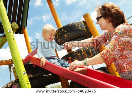 grandmother and her grandson playing on the slide on the outdoors playground - real life family - stock photo