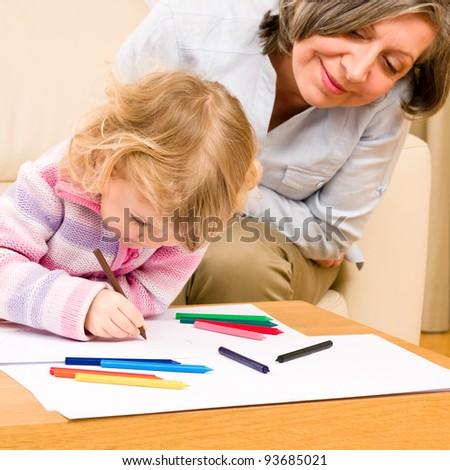 Grandmother and little girl drawing together with pencils at home - stock photo