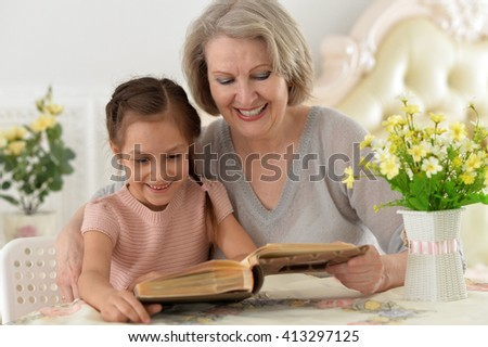 Grandmother and little girl reading book happy together at home - stock photo