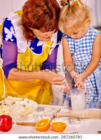 Grandmother and little granddaughter baking cookies. - stock photo