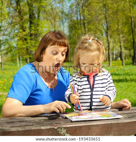 Grandmother and little granddaughter paint outdoors. Grandma is surprised drawing granddaughter. - stock photo