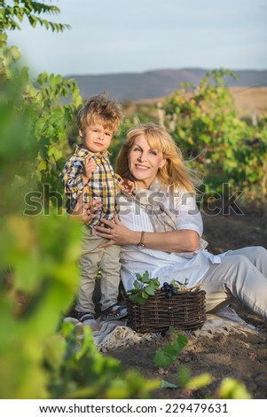 Grandmother and son sitting to the vineyard. - stock photo