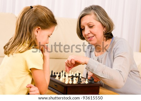Grandmother and young girl playing chess together at home - stock photo