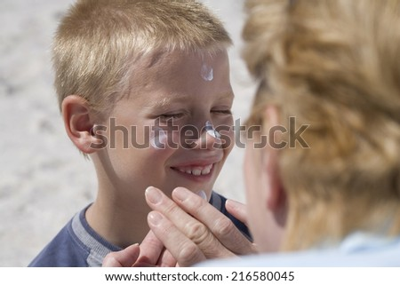 Grandmother applying sunscreen to grandson�s face - stock photo