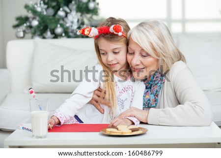 Grandmother assisting girl in writing letter to Santa Claus during Christmas at home - stock photo
