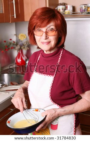 Grandmother beats eggs in a bowl and looking to camera