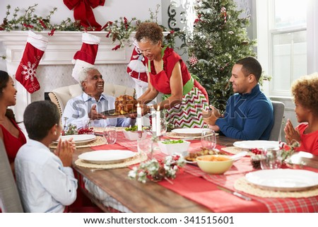Grandmother Bringing Out Turkey At Family Christmas Meal
