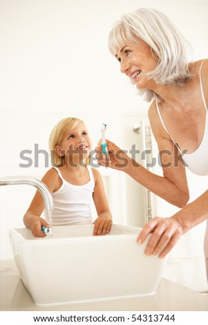Grandmother Brushing Teeth In Bathroom With Granddaughter Watching - stock photo