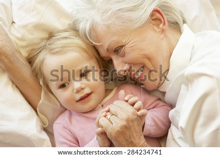 Grandmother Cuddling Granddaughter In Bed - stock photo