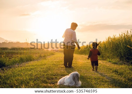 Grandmother, daughter and a dog with happy family enjoying life together at meadow; light and lens flare effect tone.