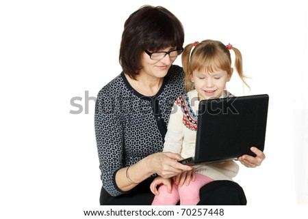 Grandmother demonstrating her granddaughter something in laptop isolated on white background - stock photo