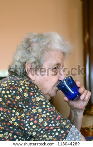 Grandmother drinks a glass of fresh water - stock photo