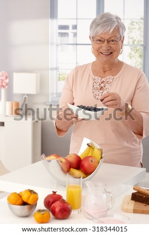 Grandmother eating blueberry, having many fruits on kitchen counter, smiling happy. - stock photo