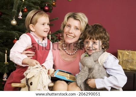 Grandmother embracing grandchildren on Christmas Eve - stock photo