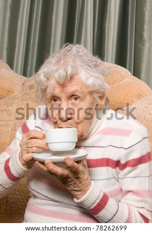Grandmother from coffee on a sofa - stock photo