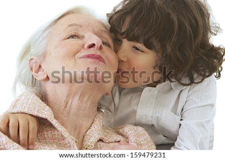 Grandmother getting a kiss from grandson. Isolated on white background.  - stock photo