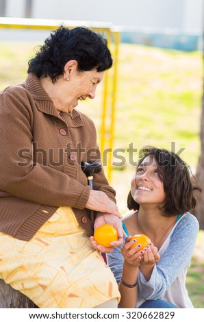 Grandmother granddaughter quality time outdoors holding an orange. - stock photo
