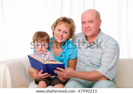 Grandmother, grandfather and grandson reading a book together. Symbol of the family. - stock photo