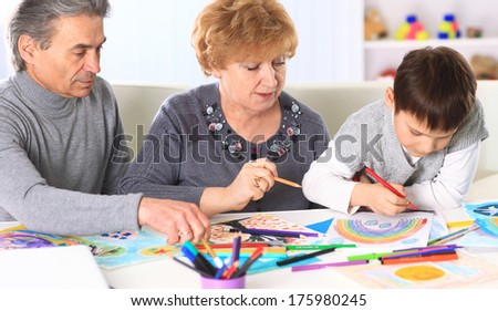 Grandmother, grandfather and grandson spend time together. Symbol of the family. - stock photo