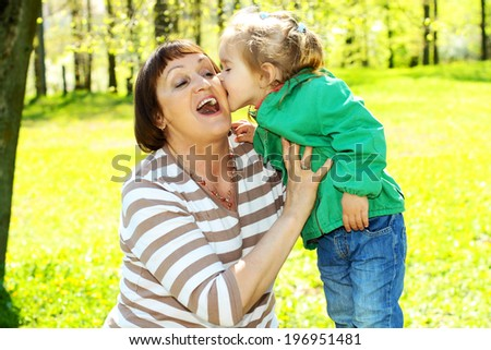 Grandmother has fun with a pretty little granddaughter on the background of yellow dandelions. Granddaughter playfully bites his grandmother - stock photo