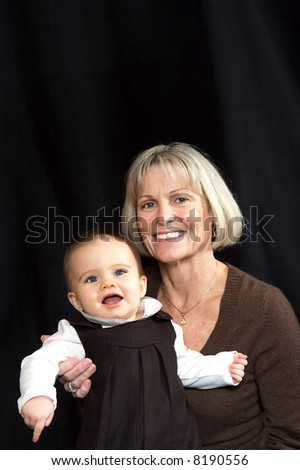 Grandmother holding granddaughter both smiling - stock photo