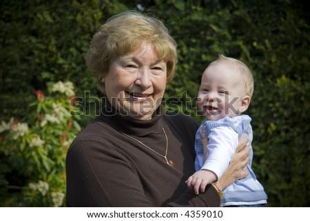 Grandmother holding her grandson portrait in garden - stock photo