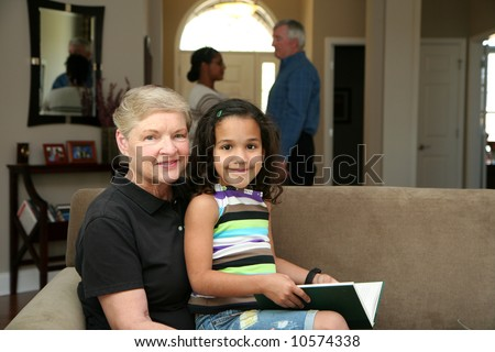 Grandmother holds her granddaughter while she reads a book - stock photo