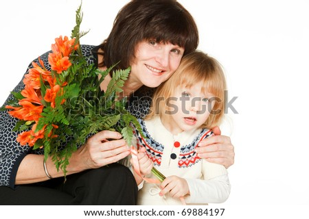 Grandmother hugging her granddaughter that have presented her the bunch of flowers, isolated on white - stock photo