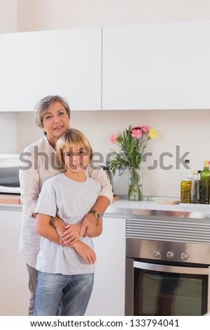 Grandmother hugging her grandson in kitchen - stock photo