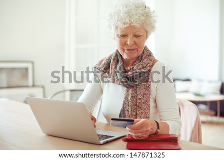 Grandmother in front of laptop paying online using a credit card - stock photo