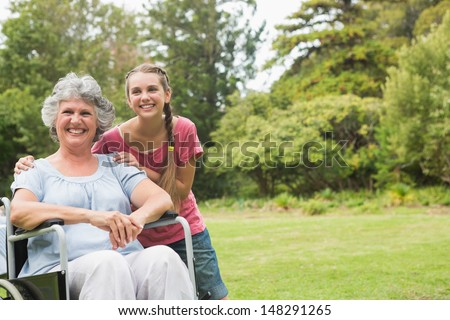 Grandmother in wheelchair and granddaughter smiling into the camera in the park on sunny day - stock photo