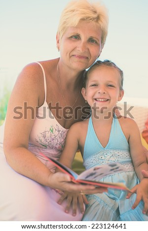 Grandmother is reading a book to her granddaughter - stock photo