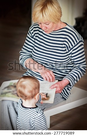 Grandmother is reading book to her grandson, both are in stripped vests. Image with selective focus - stock photo