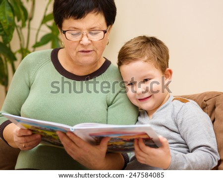 Grandmother is reading book with her grandson, indoors - stock photo