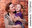 Grandmother kissing her grand daughter against brick wall - stock photo