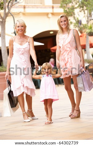 Grandmother, Mother And Daughter Enjoying Shopping Trip Together