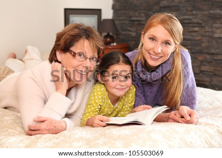 Grandmother, mother, and daughter lying on a bed - stock photo